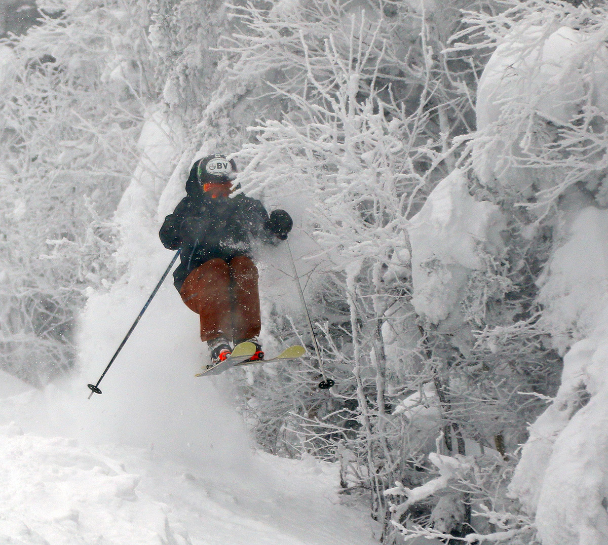 An image of Ty as he about to jump through some tree branches on the Hard Luck trail during Winter Storm Malcolm at Bolton Valley Ski Resort in Vermont