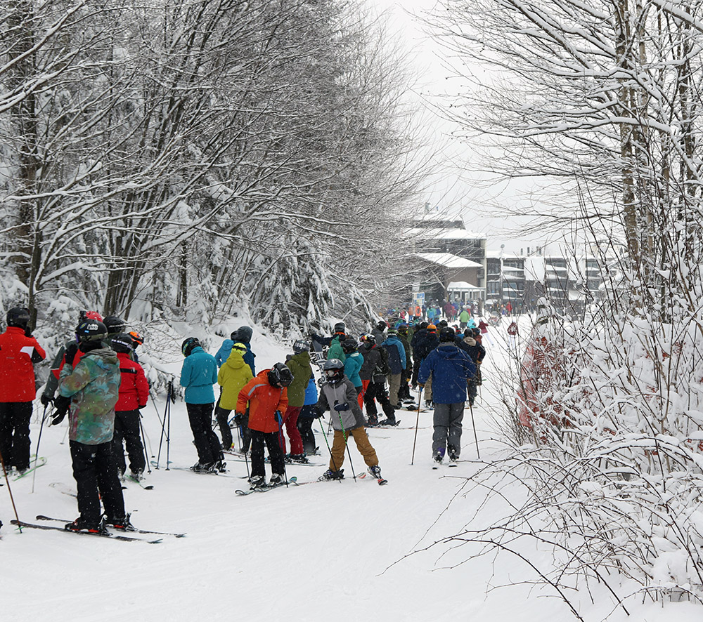 An image of a line of people waiting for the Wilderness Double Chair to open for the first time during the 2020-2021 ski season at Bolton Valley Ski Resort in Vermont