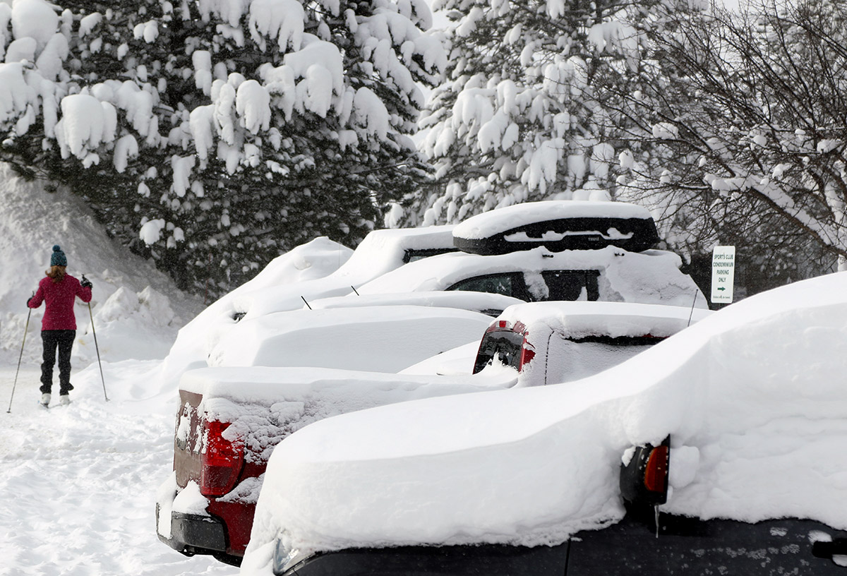 A snowy scene with a skier and cars from the Village area of Bolton Valley Ski Resort in Vermont after some January snowstorms