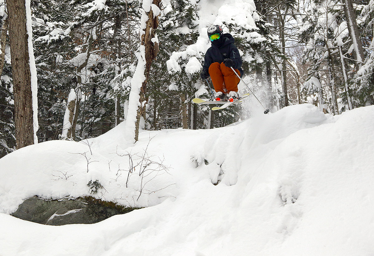 An image of Ty jumping off a ledge on skis in the Wood's Hole area of Bolton Valley Ski Resort in Vermont