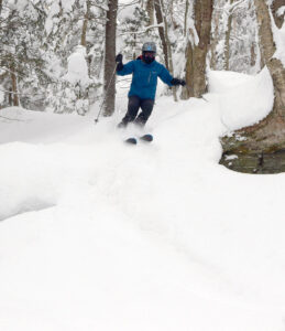 An image of Erica skiing powder from Winter Storm Peggy in the Wood's Hole area at Bolton Valley Ski Resort in Vermont