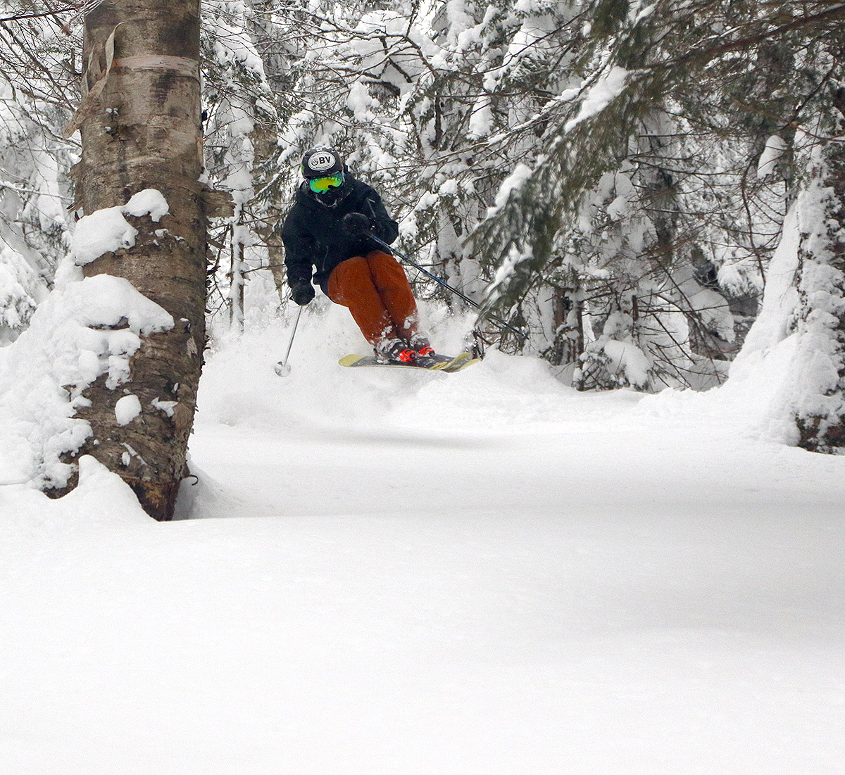 An image of Ty jumping into some untracked powder in a ski line off The Knob at Bolton Valley Ski Resort in Vermont