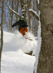 An image of Ty dropping off a ledge while powder skiing after Winter Storm Roland at Bolton Valley Ski Resort in Vermont