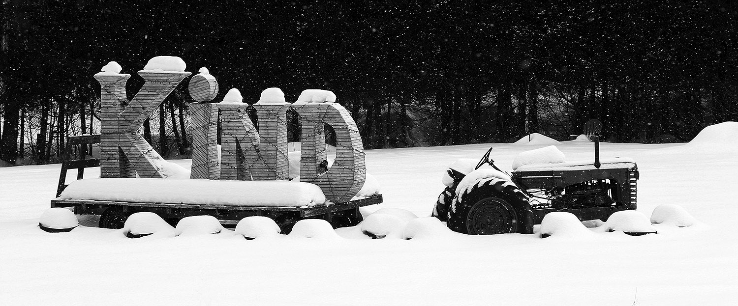 "An image of a tractor pulling a sled in the snow with the word ""KIND"" spelled out among midwinter snow in the Waterbury Center area of Vermont"