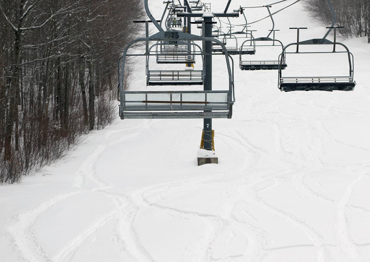 An image showing ski tracks in powder snow below the Timberline Chairlift at Bolton Valley Ski Resort in Vermont