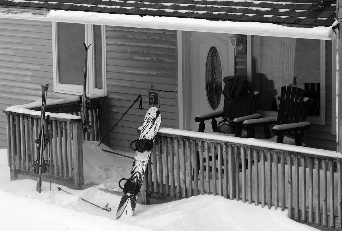 An image of ski gear in the snow on a porch outside a condominium during a March snowstorm at Bolton Valley Ski Resort in Vermont