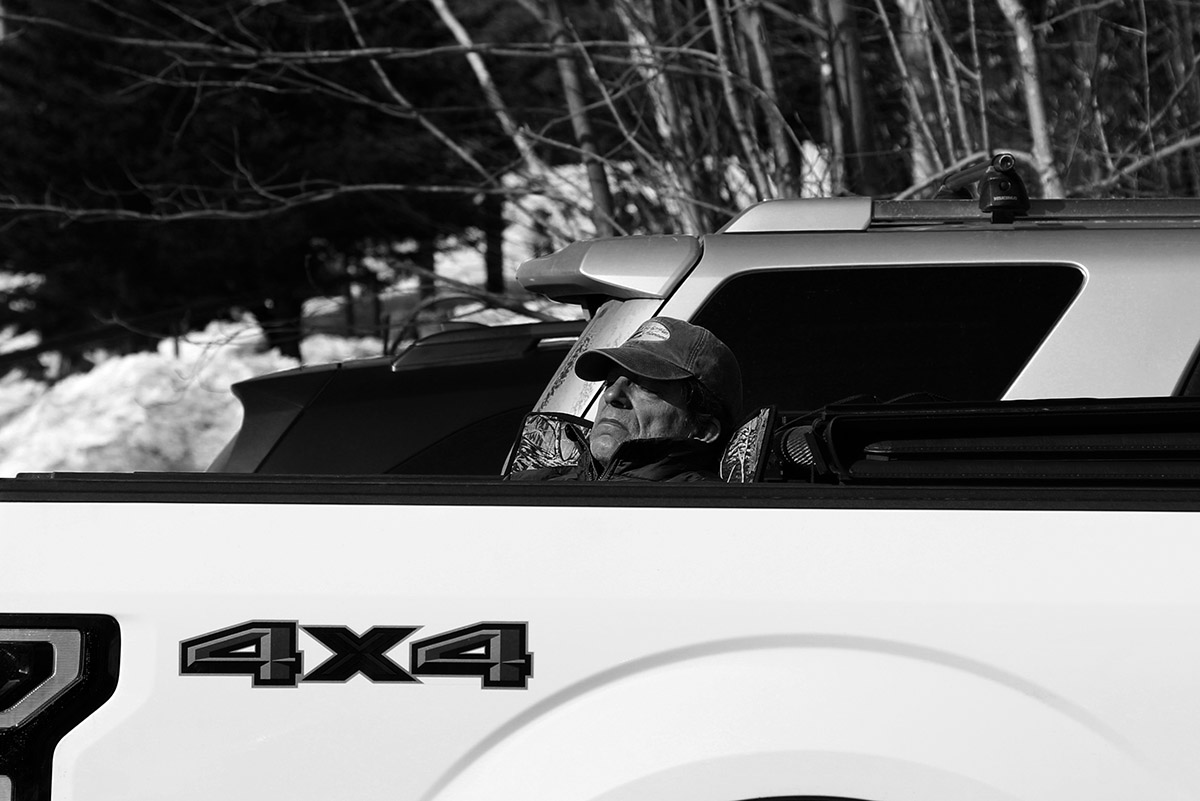 An image of a man napping in the sun in the back of his pickup truck at the Timberline Base area of Bolton Valley Ski Resort in Vermont