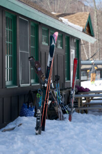 An image of skis stuck in the snow outside the Timberline Base Lodge on a sunny spring day at Bolton Valley Ski Resort in Vermont