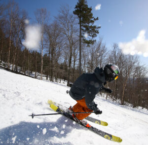 An image of Ty skiing down the Showtime trail with spring snow at Bolton Valley Ski Resort in Vermont