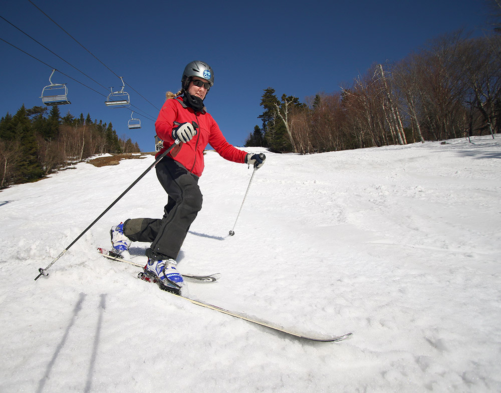 An image of Erica Telemark skiing in spring snow on a sunny day at Bolton Valley Ski Resort in Vermont