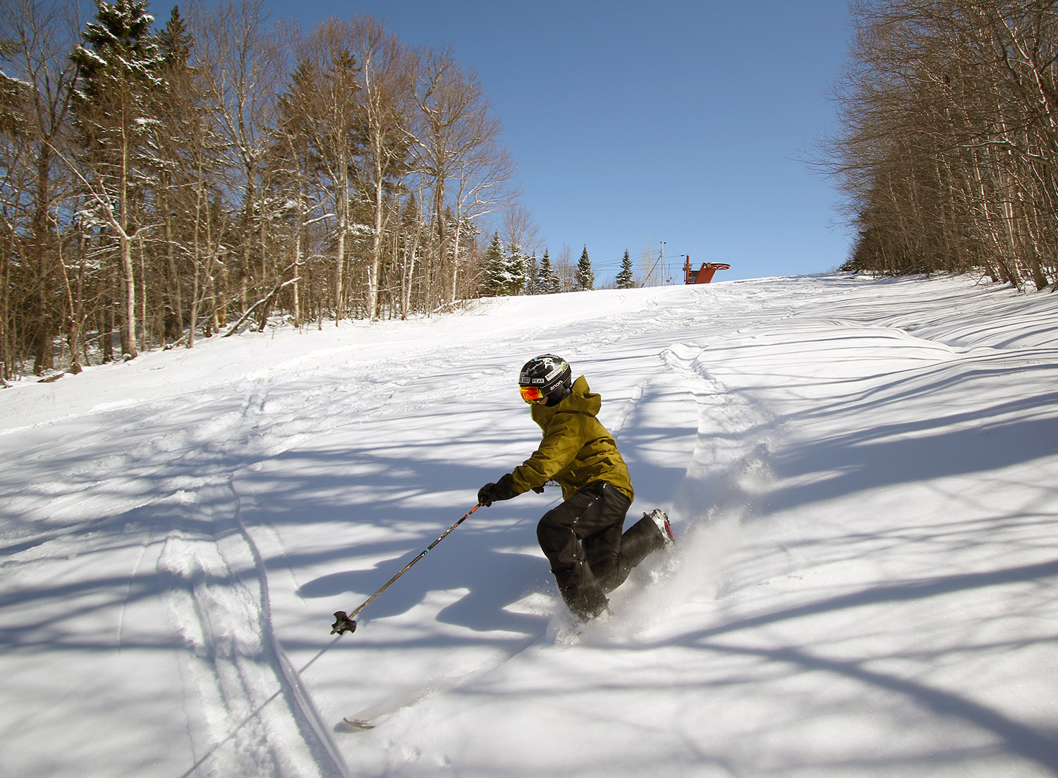 An image of Jay Telemark skiing in powder after an April snowstorm at Bolton Valley Ski Resort in Vermont