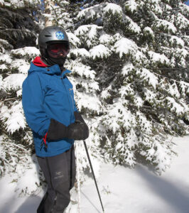An image of Erica standing by some snowy evergreens after an April snowstorm at Bolton Valley Ski Resort in Vermont