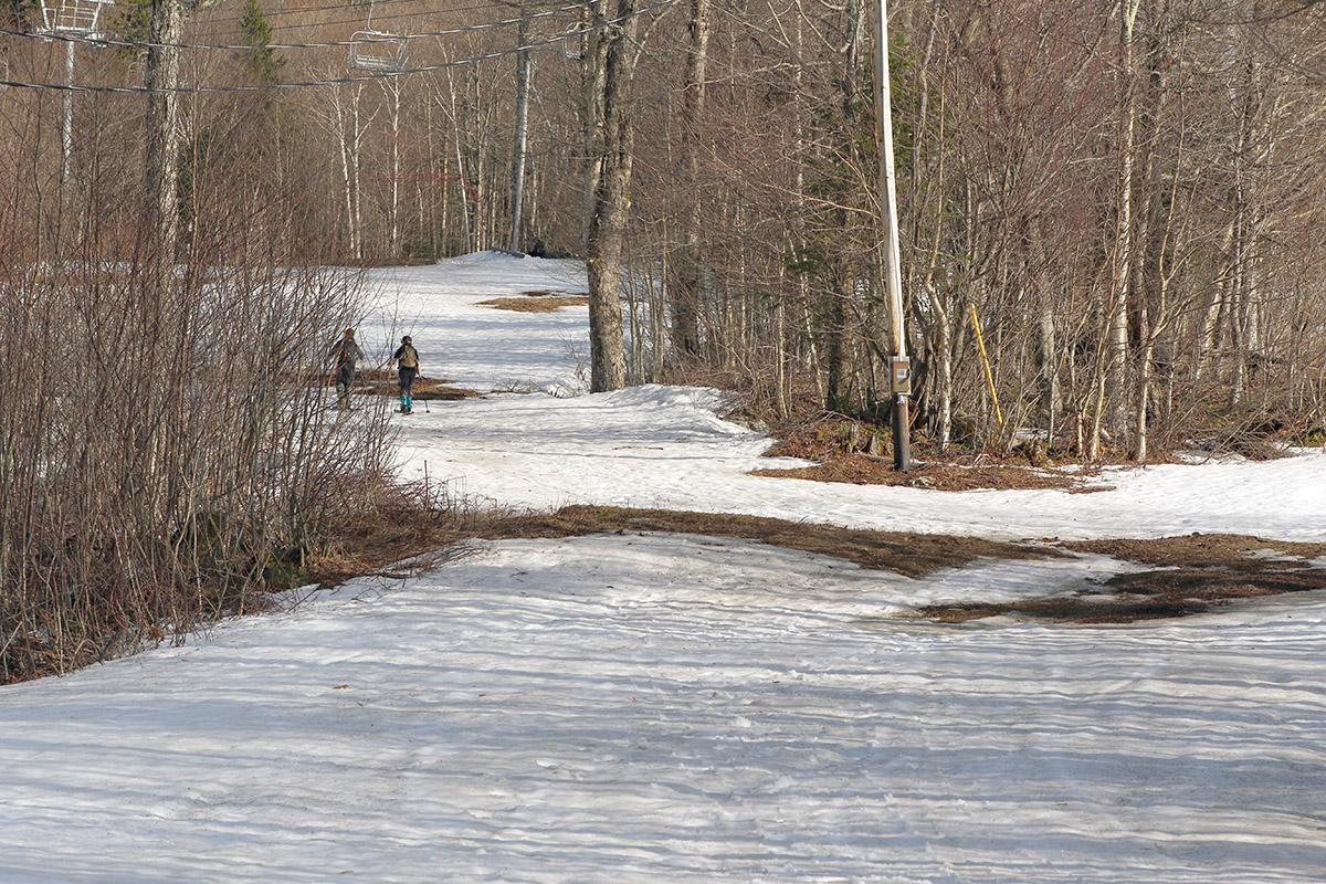 An image of a couple of skiers ascending on skins through the Hide Away Terrain Park on an April day at Bolton Valley Ski Resort in Vermont