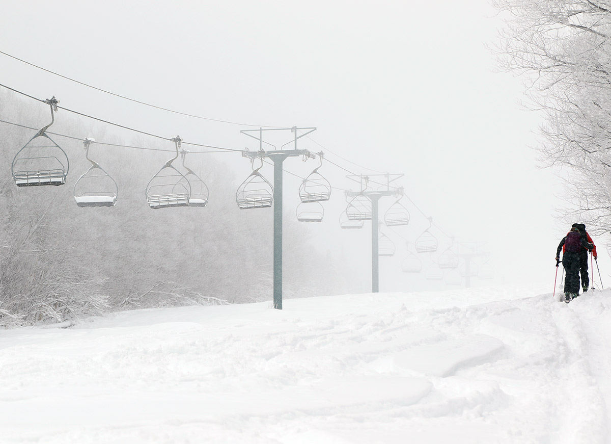 An image of skiers skinning up the Pike trail after an April snowstorm at Pico Mountain Ski Resort in Vermont