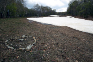 An image of the Lower Standard trail with late-season leftover snow in mid-May at Stowe Mountain Ski Resort in Vermont